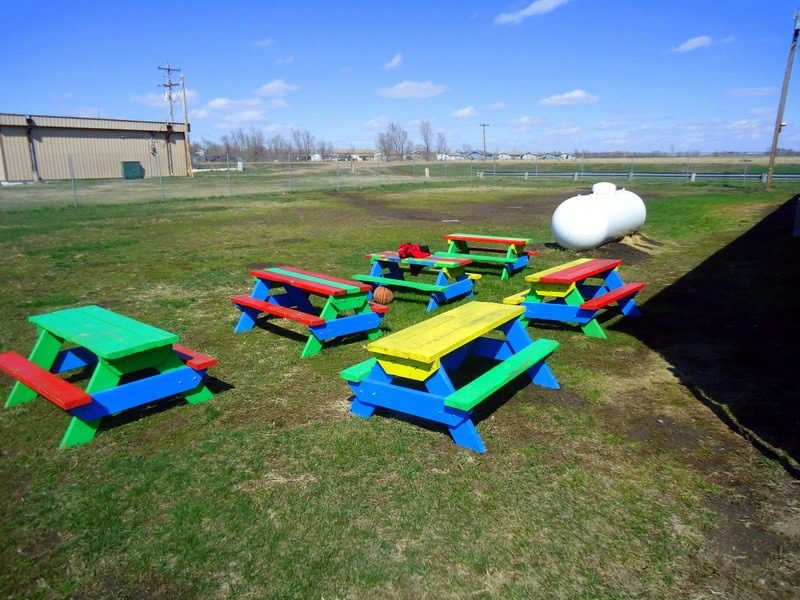 Colorful picnic tables in the back yard of the Boys and Girls Club of Three Districts.