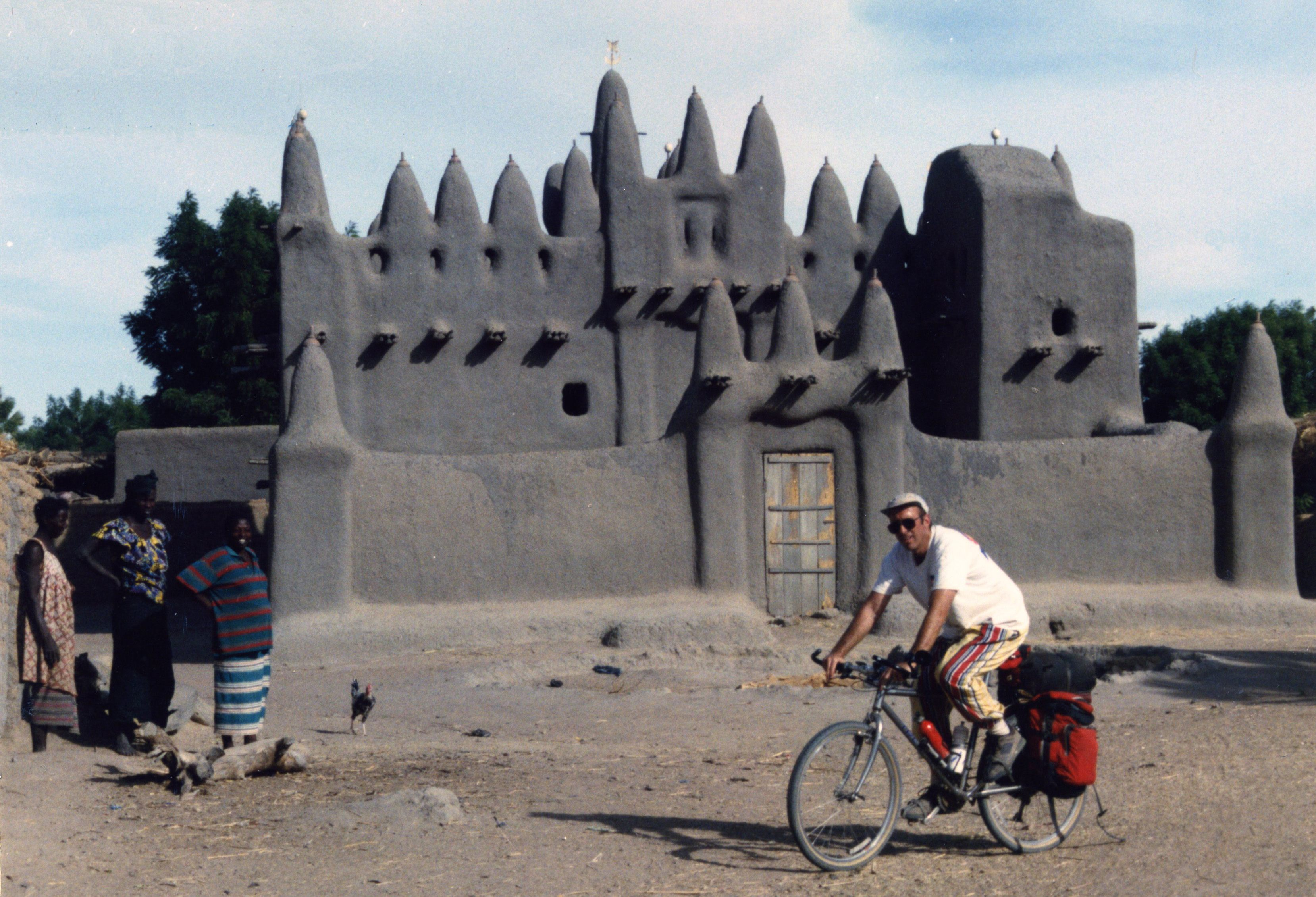 John cycling past a mud brick mosque in Mali in 1996.