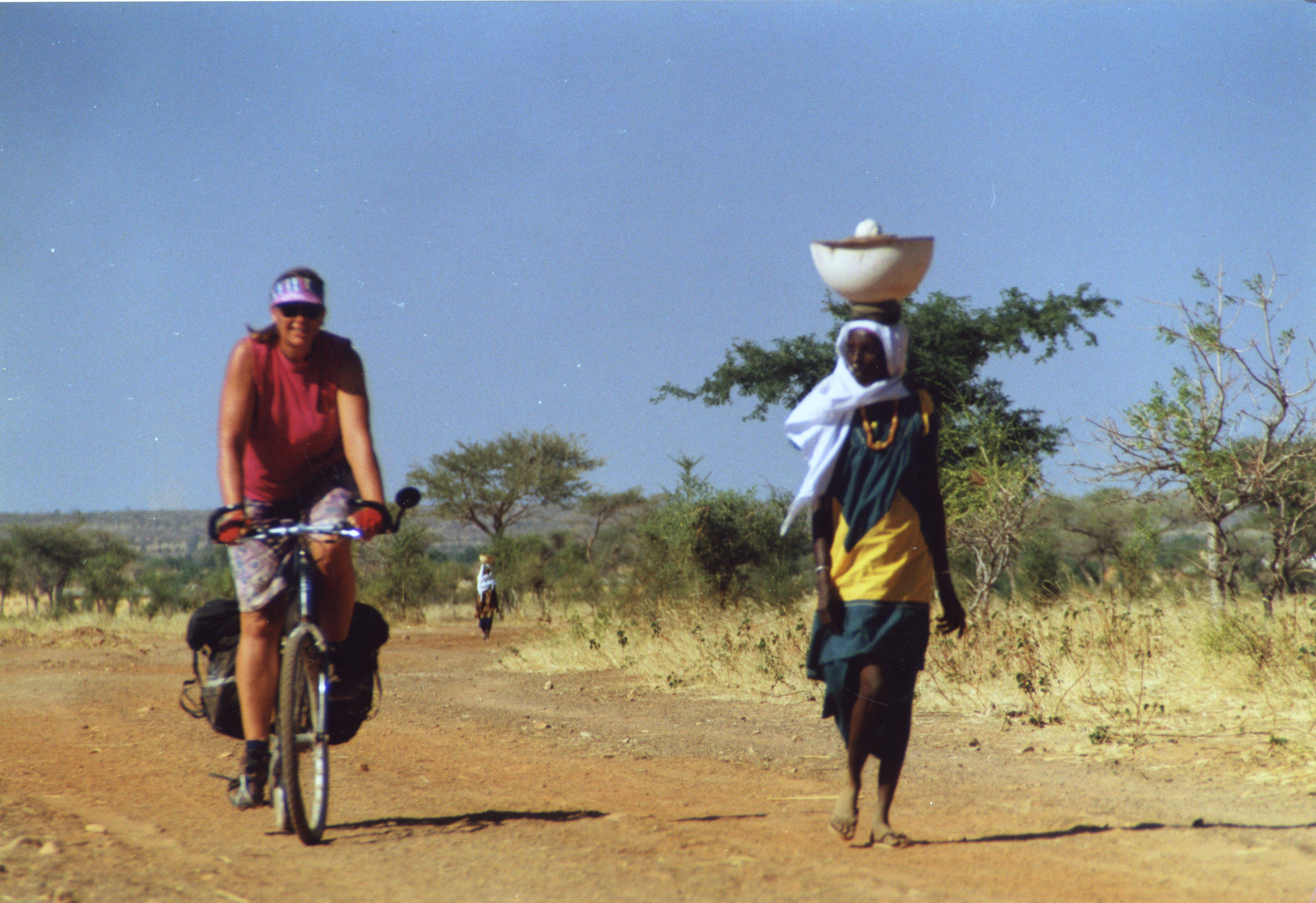 """Nancy Explains: """"Me cycling in Mali. We had the brilliant idea of taking off across a dirt road the map showed cutting through the desert. As we progressed farther, the road condition deteriorated and eventually the road turned into nothing more than a small trail. People assured us that Djenne was """"that way"""" so we kept going - for about 80 miles along the little trail going through the desert. We were thrilled when we finally emerged from the desert!"""""""