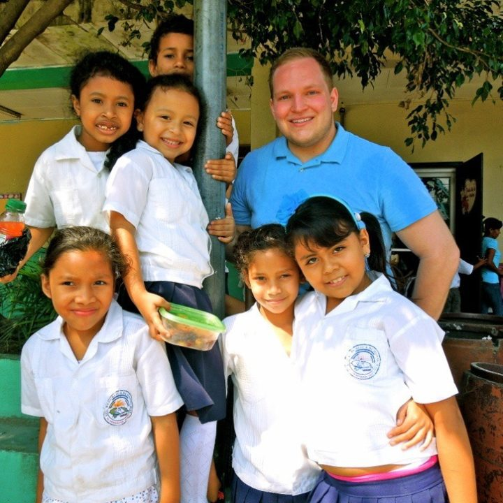 Matt in Honduras, taking a break from painting to spend time with some students.