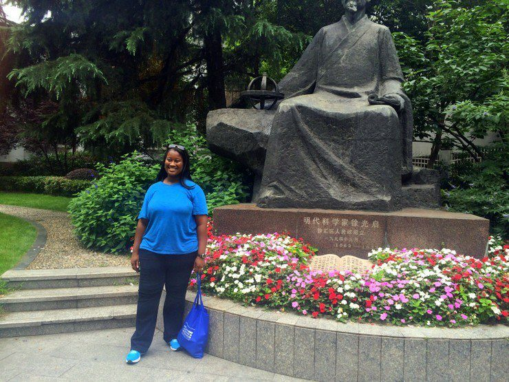 Candace in China with a larger-than-life statue of the famous scientist, farmer, and political figure, Xu Guangqi.
