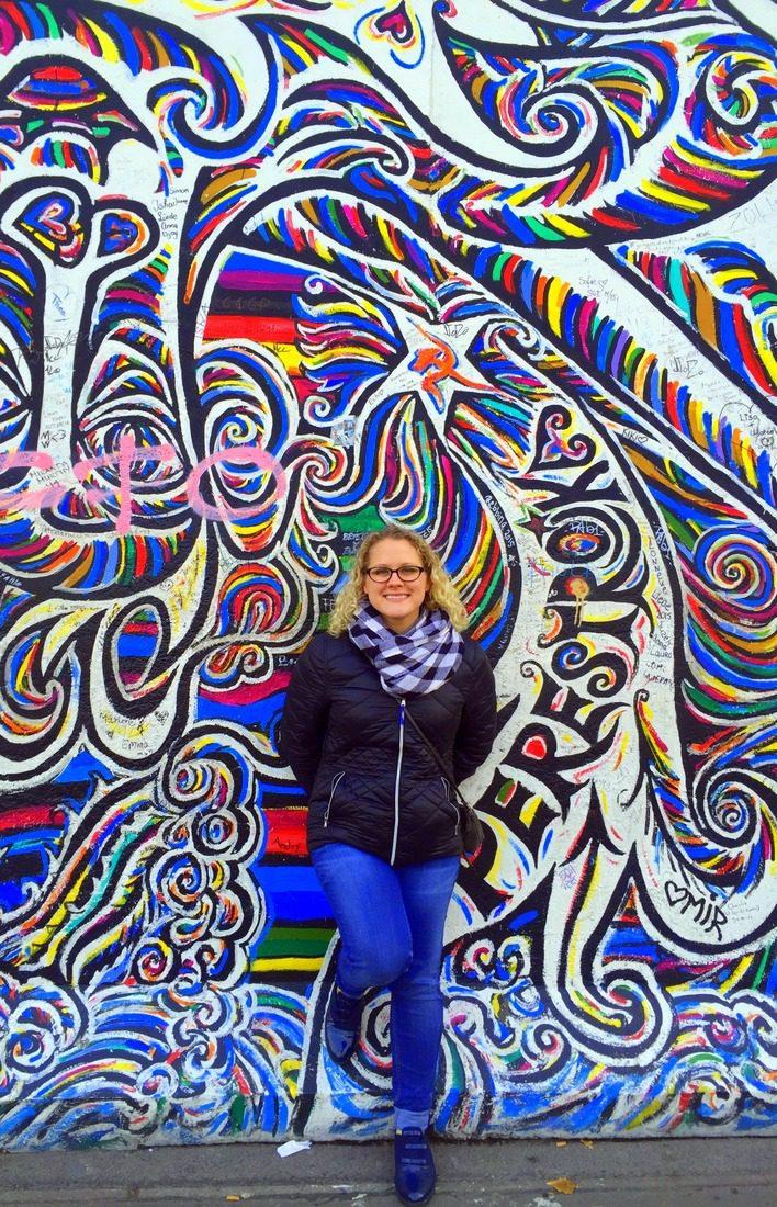 By a beautiful mural in Berlin, Germany.