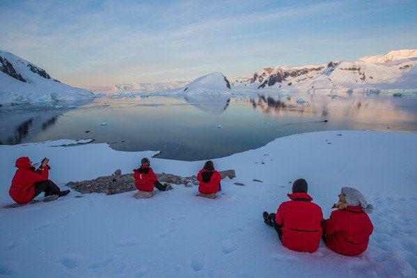 Travelers gazing at the sunset on Ronge Island, Antarctica.