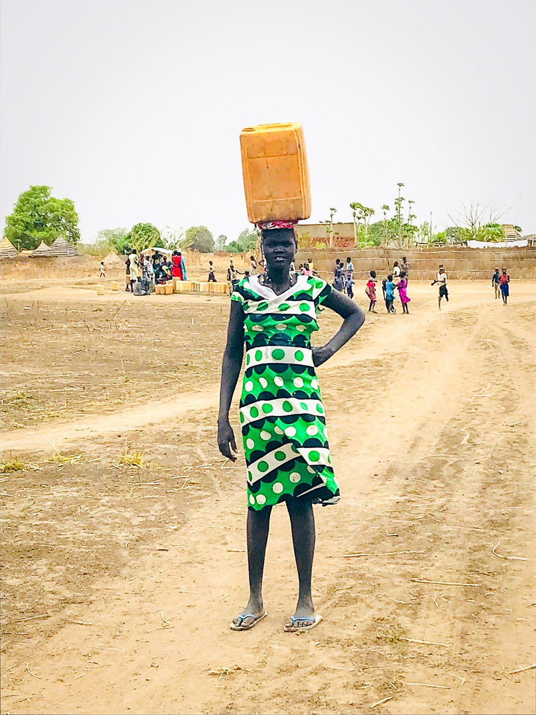 A girl in South Sudan carrying water on her head.