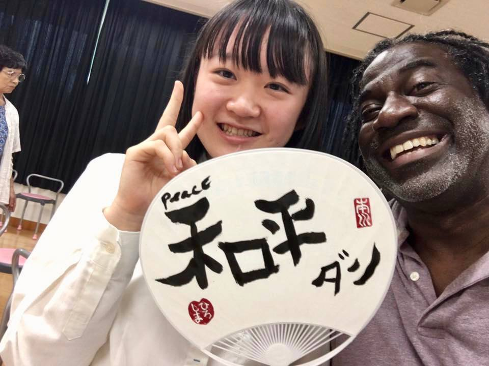 Dunn with a student in Japan, after she taught him to write his name in Japanese.